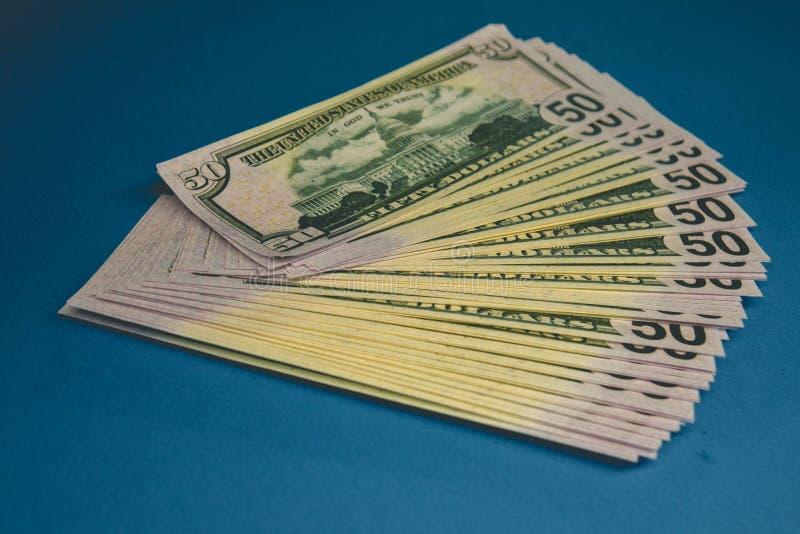 Pak van vijftig die dollarsbankbiljetten op blauwe achtergrond worden ge?soleerd