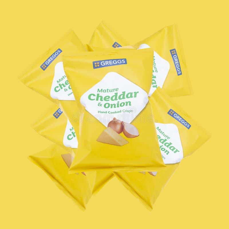 Paket av Greggs mogen cheddar och lagade mat chipset för lök det hand på en gul bakgrund royaltyfri bild