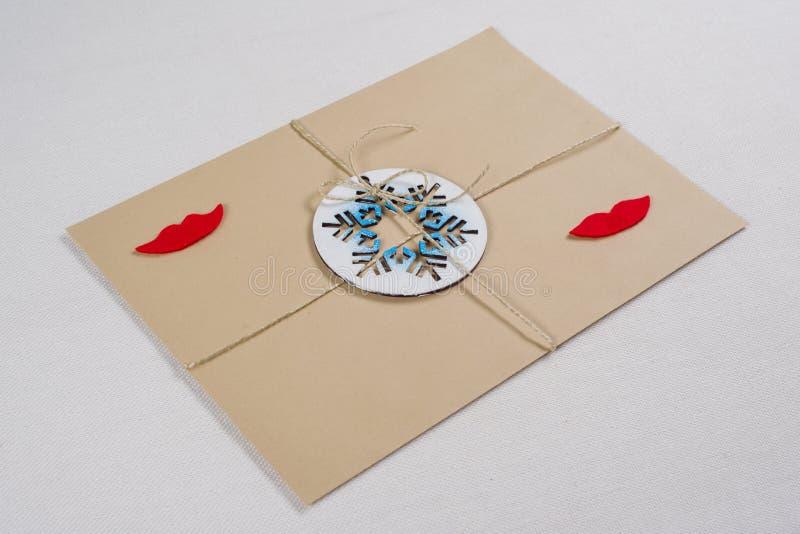 Paket, Buchstabe, verpackte in einem Weinleseumschlag mit einer symbolischen Schneeflocke Neues Jahr und Weihnachtsfeiertage lizenzfreies stockbild
