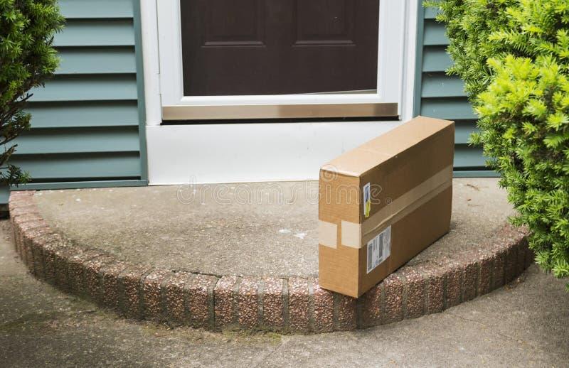 Paket gelassen auf krummem Rücken durch Haustür lizenzfreie stockbilder