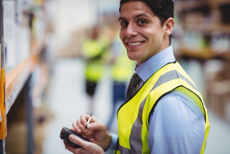 Pakhuisarbeider die handscanner met behulp van stock afbeelding
