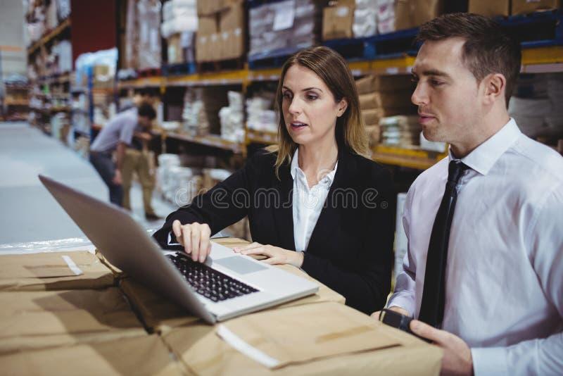 Pakhuismanagers die laptop met behulp van stock fotografie