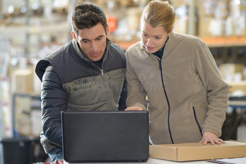 Pakhuismanagers die laptop in pakhuis met behulp van royalty-vrije stock afbeeldingen