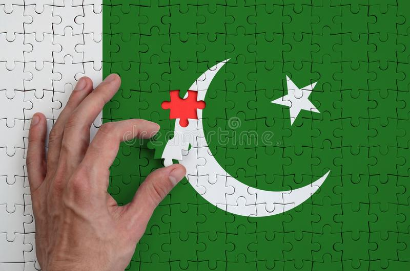 Pakistan flag is depicted on a puzzle, which the man`s hand completes to fold stock photography