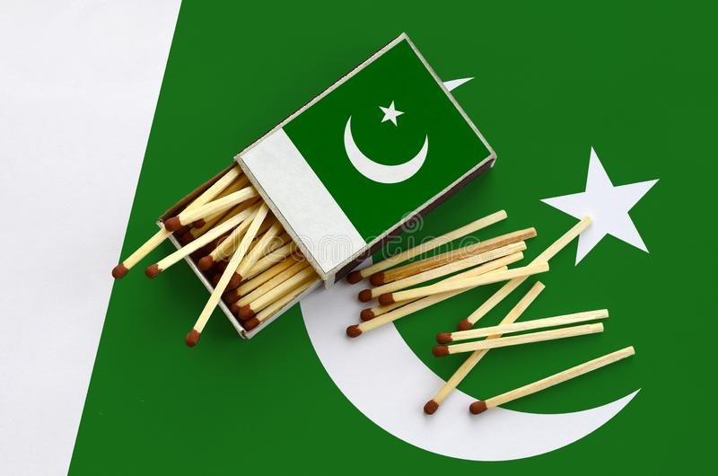 Pakistan flag is shown on an open matchbox, from which several matches fall and lies on a large flag royalty free stock photos