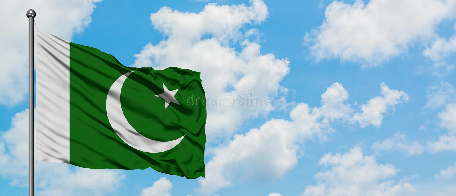 Pakistan flag waving in the wind against white cloudy blue sky. Diplomacy concept, international relations.  stock photo