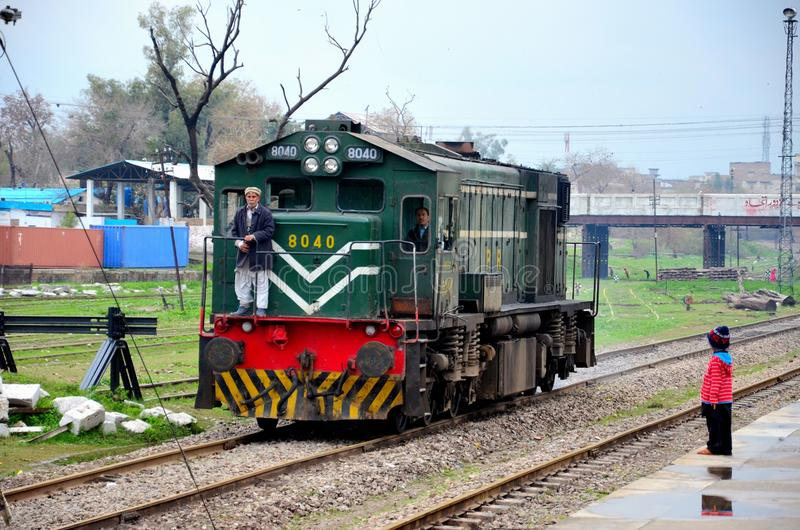 Pakistan Railways locomotive engine passes as small child watches stock images