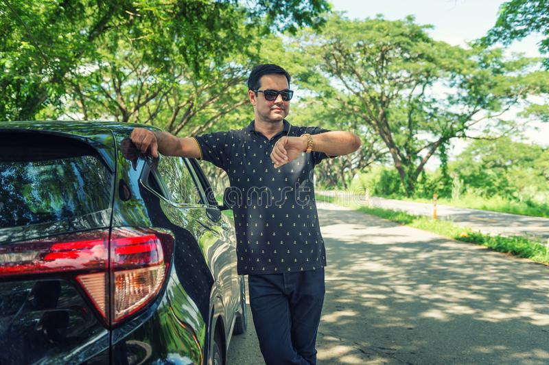 Pakistani muslim Man standing near car and looking watch is wait royalty free stock photography