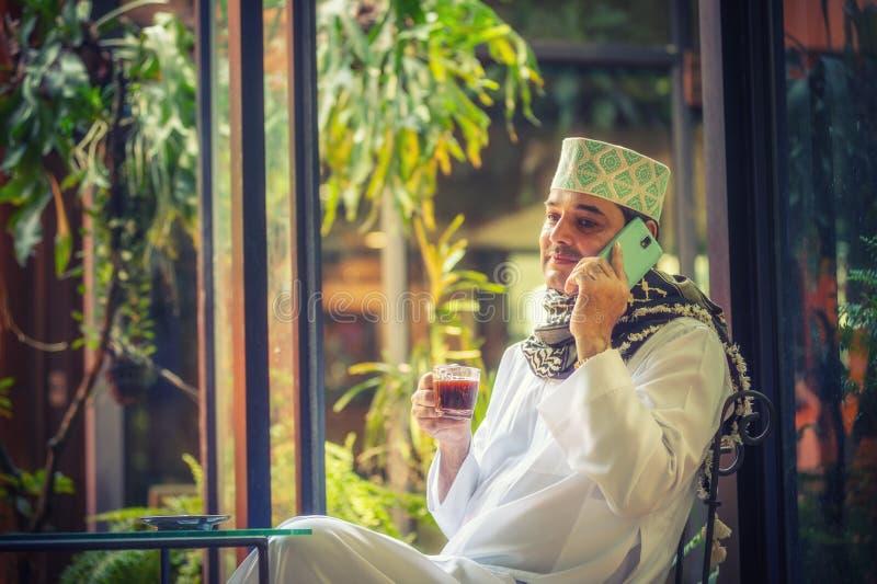 Pakistansk muslimaffärsman som talar på mobiltelefonen och att dricka arkivfoton