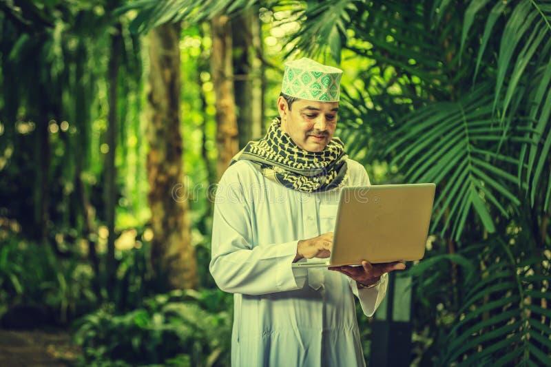 Pakistansk muslimmanställning och arbete på anteckningsboken royaltyfri fotografi