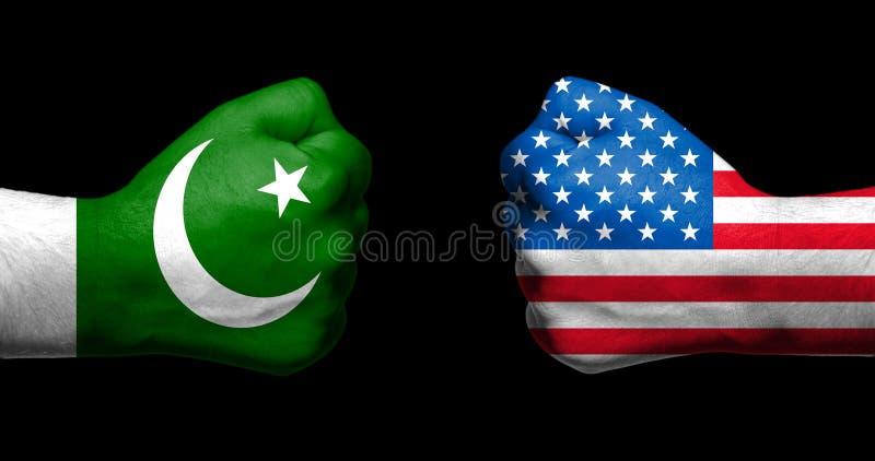 Pakistanska flaggor och Förenta staterna som målades på två, grep hårt om näven royaltyfri foto