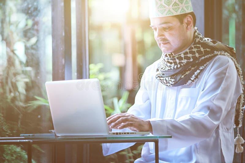 Pakistanska muslim Man arbete på bärbara datorn i kafé royaltyfria bilder