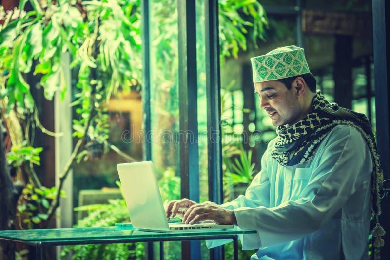 Pakistanska muslim Man arbete på bärbara datorn i kafé royaltyfri fotografi