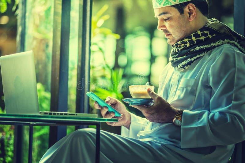 Pakistanska muslim Man genom att använda mobiltelefonen och dricka kaffe i kafé fotografering för bildbyråer