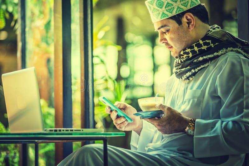 Pakistanska muslim Man genom att använda mobiltelefonen och dricka kaffe i kafé royaltyfria foton