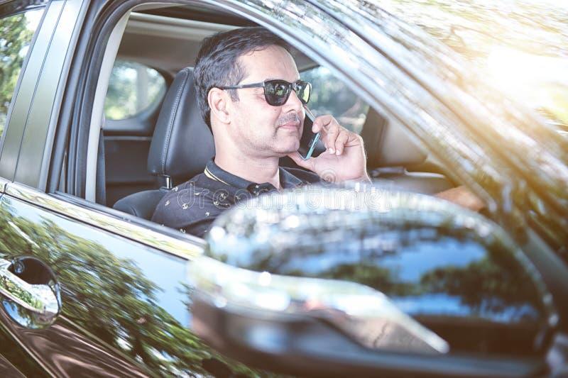 Pakistanska muslim Man körning av bilen och samtal på den conc mobiltelefonen royaltyfri fotografi