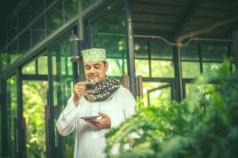 Pakistanskt muslimmananseende och drickakaffe arkivfoton