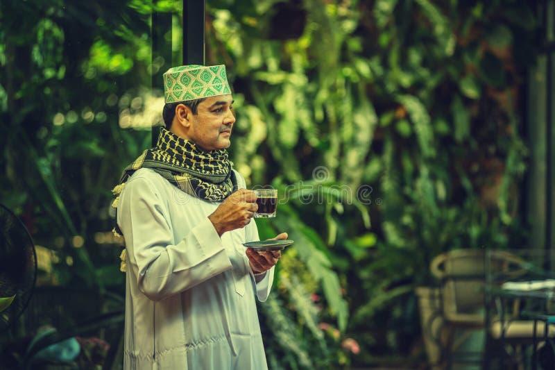 Pakistanskt muslimmananseende och drickakaffe fotografering för bildbyråer