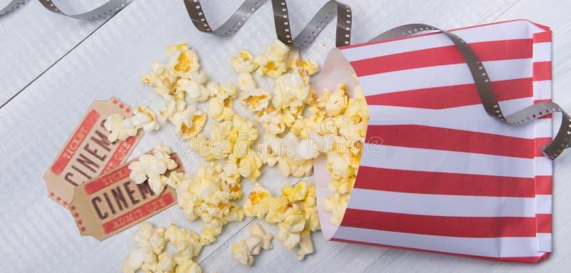 Pakket met verspreide popcorn, twee filmkaartjes en film, op een lichtgrijze achtergrond, close-up stock afbeeldingen