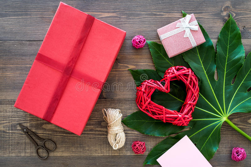 Pakować prezent Czerwony prezenta pudełko, sciccors, cienki sznur na ciemnego drewnianego tła odgórnym widoku obrazy stock