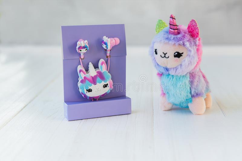 Pakujący lamy jednorożec hełmofony dla dzieciaków w purpury jucznej i barwionej pluszowej lamy jednorożec na białym drewnianym tl obrazy stock