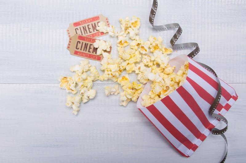 Pakunek z rozrzuconym popkornem, dwa filmów biletami i filmem, na świetle - szary tło fotografia stock