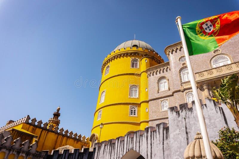 Pal?cio de Pena em Sintra e na bandeira portuguesa que acenam no vento portugal fotografia de stock royalty free