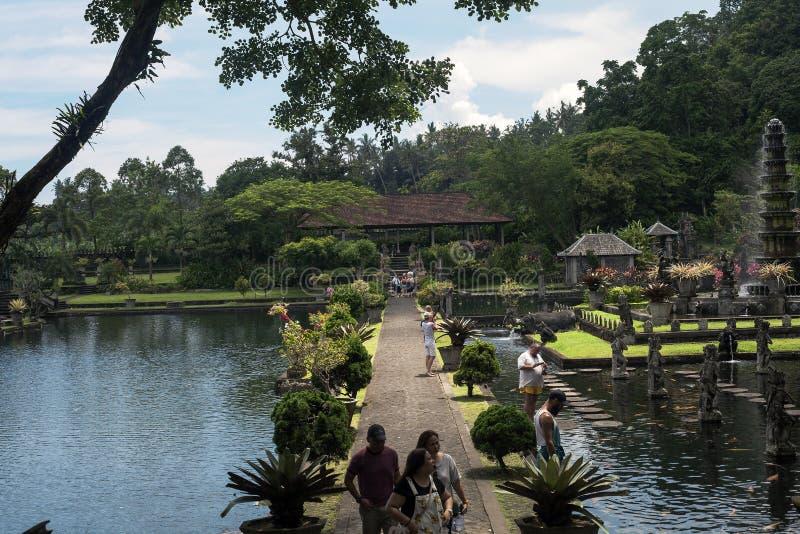 Palácio real da água de Tirta Gangga antigo e turistas de passeio imagens de stock