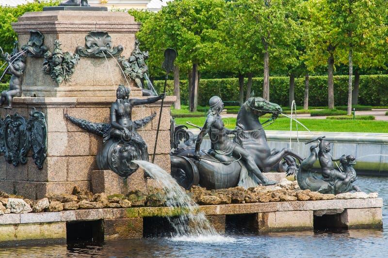 Palácio St Petersburg de Peterhof, Rússia Detalhes de fonte de Netuno no jardim superior O palácio de Peterhof incluído no fotos de stock royalty free