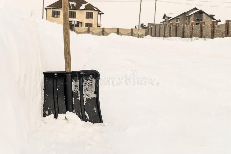 Pala de la nieve cerca de una nieve acumulada por la ventisca por el camino en un área residencial suburbana de cintura baja imagen de archivo