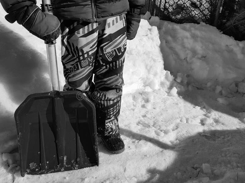 Pala de la nieve en las manos - el ni?o limpia la nieve en invierno o primavera imagen de archivo
