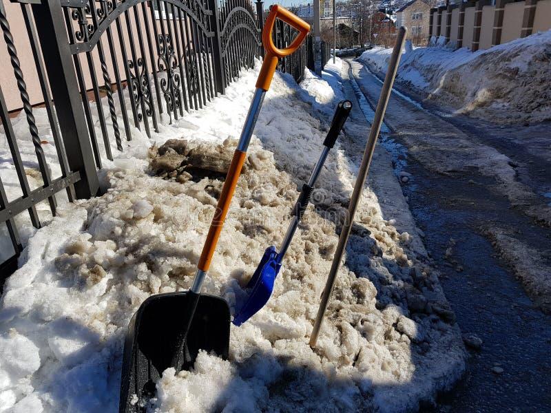 Pala della neve ed ascia di ghiaccio nella neve contro lo sfondo delle mattonelle e recintare primavera o inverno fotografia stock libera da diritti