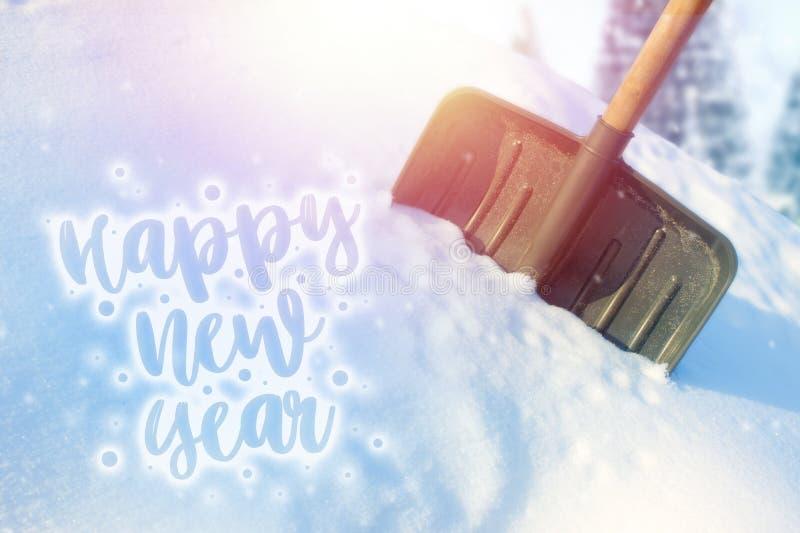 Pala en una nieve acumulada por la ventisca, día soleado de la nieve La inscripción en la Feliz Año Nuevo de la nieve foto de archivo