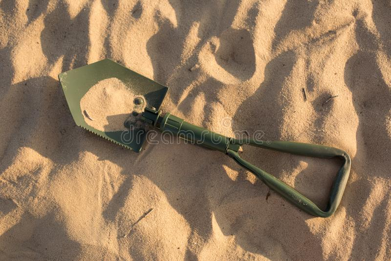 Pala que marcha Pala en la arena Pala verde imagen de archivo