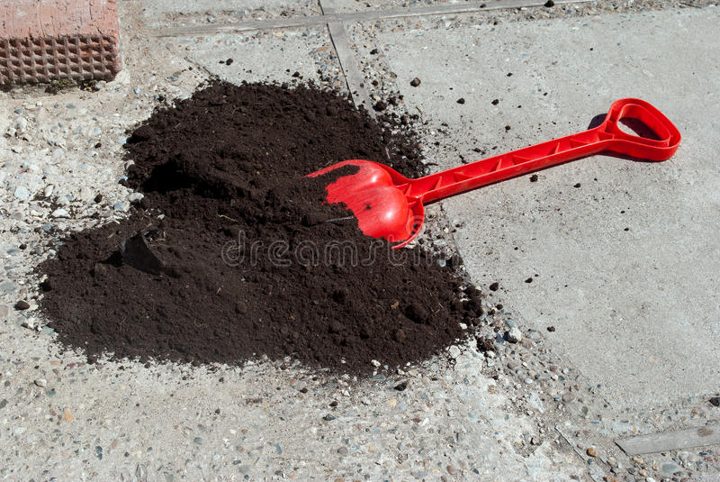 Pala rossa di plastica con terra nera immagine stock