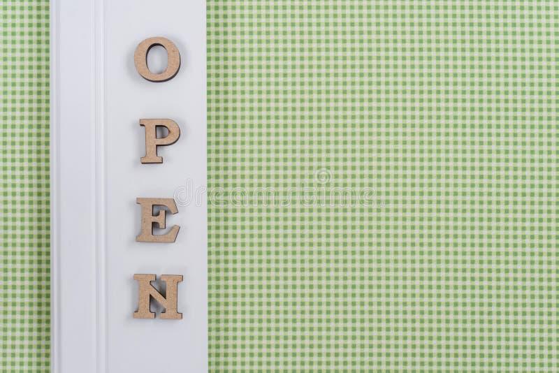 Palabra abierta, letras de madera abstractas, fondo verde del blanco de la jaula foto de archivo