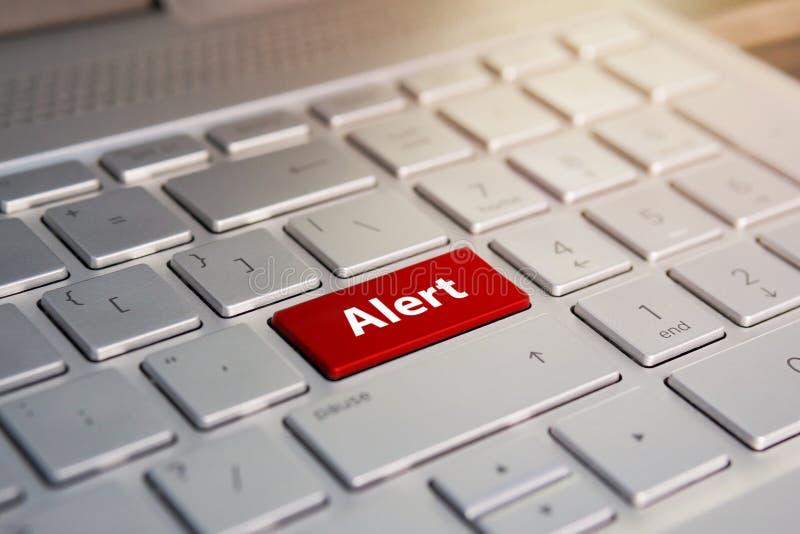 Palabra alerta en el botón rojo del teclado, botón del color en el teclado de plata gris del ultrabook moderno subtítulo en el bo foto de archivo