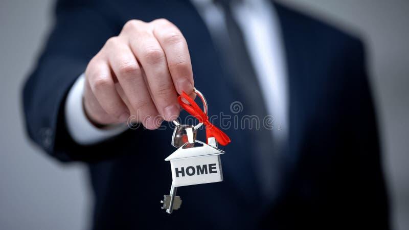 Palabra casera en llavero en la mano del hombre de negocios, compra de la casa, servicios de alquiler imagen de archivo libre de regalías