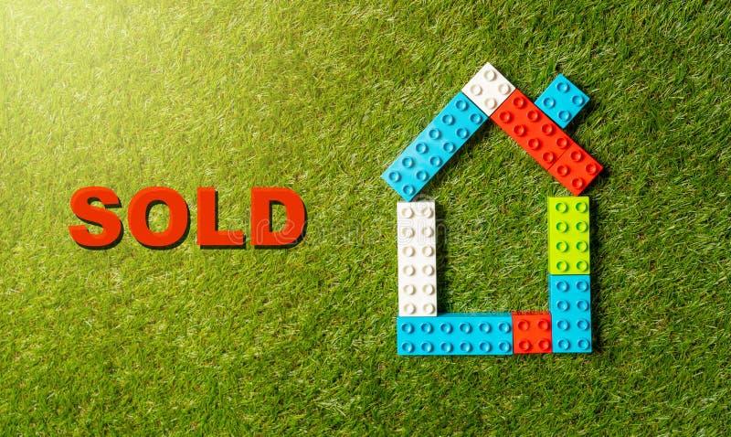 Palabra colorida Sold de la casa de bloques del juguete escrita en hierba en concepto de la industria de los bienes inmuebles y d ilustración del vector