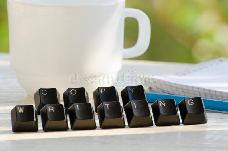 Palabra de Copywriting de llaves en una tabla blanca, taza del té imagen de archivo