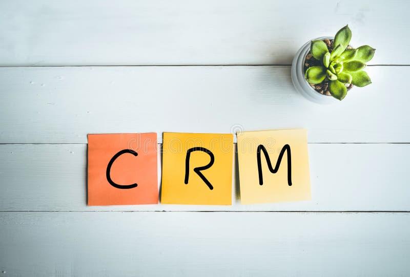 Palabra de CRM con la nota de papel sobre el fondo de madera blanco de la tabla fotografía de archivo libre de regalías