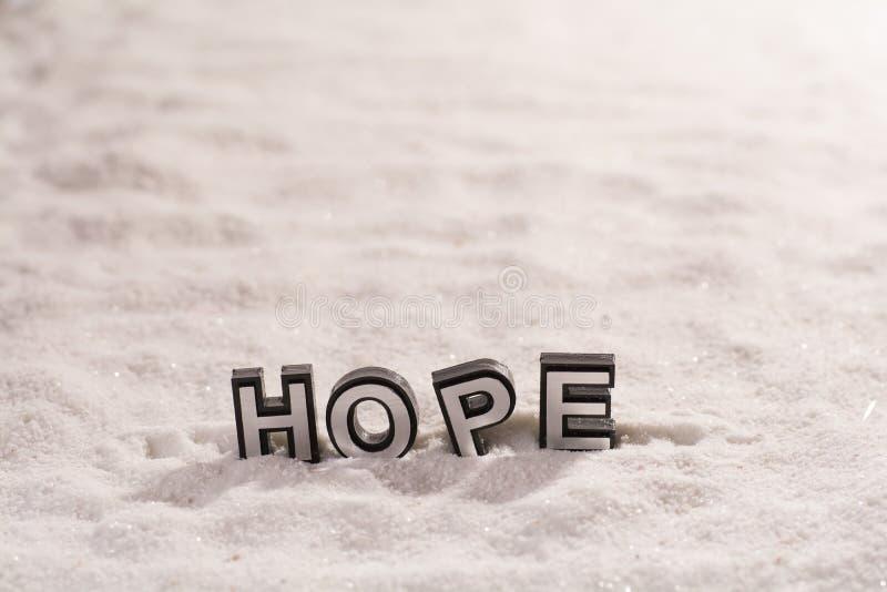 Palabra de la esperanza en la arena blanca fotografía de archivo libre de regalías