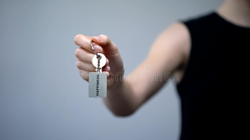 Palabra de la felicidad en llavero en la mano femenina, logro independiente del éxito imagen de archivo libre de regalías