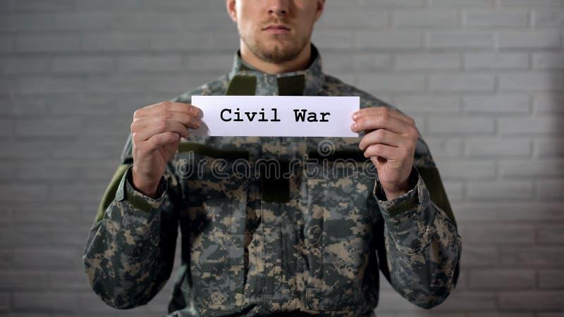 Palabra de la guerra civil escrita en las manos de la muestra adentro del soldado de sexo masculino, de la crueldad y de la muert fotos de archivo libres de regalías