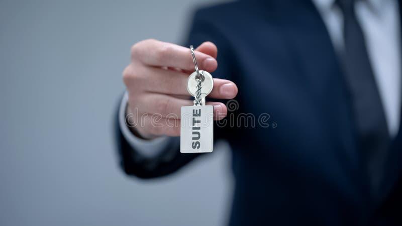 Palabra de la habitación en llavero en la mano del hombre de negocios, alojamiento superior de alquiler de la calidad fotografía de archivo