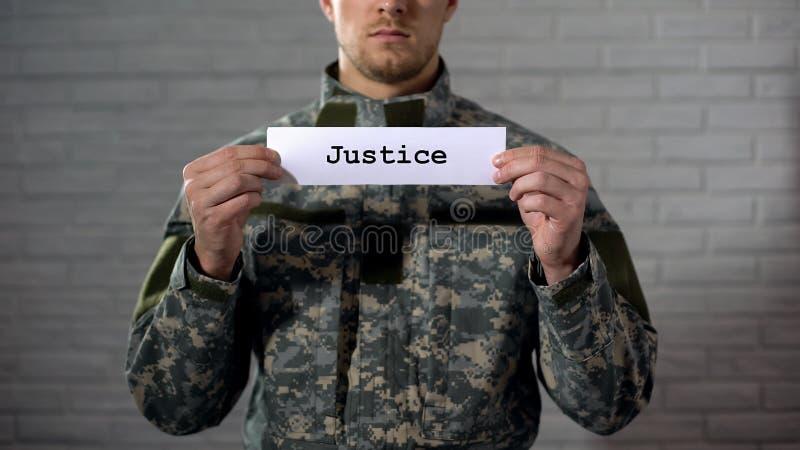 Palabra de la justicia escrita en las manos de la muestra adentro del soldado de sexo masculino, tribunal militar, tribunal imágenes de archivo libres de regalías