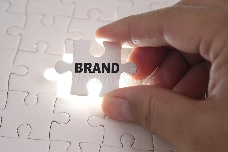 Palabra de la marca en rompecabezas Manos del hombre de negocios que llevan a cabo el puz blanco imagenes de archivo