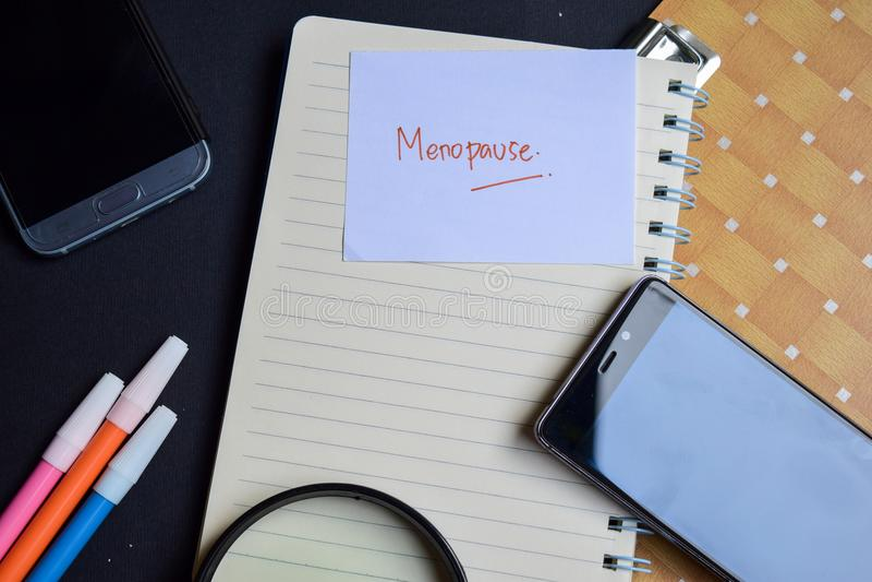 Palabra de la menopausia escrita en el papel texto en el libro de trabajo, concepto de la menopausia del negocio de la tecnología foto de archivo libre de regalías