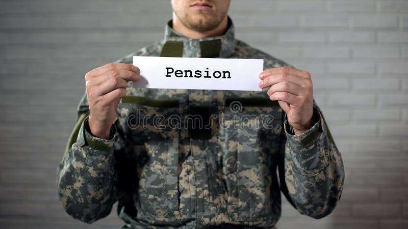 Palabra de la pensión escrita en las manos del soldado de sexo masculino, pagos de la muestra adentro del retiro imagenes de archivo