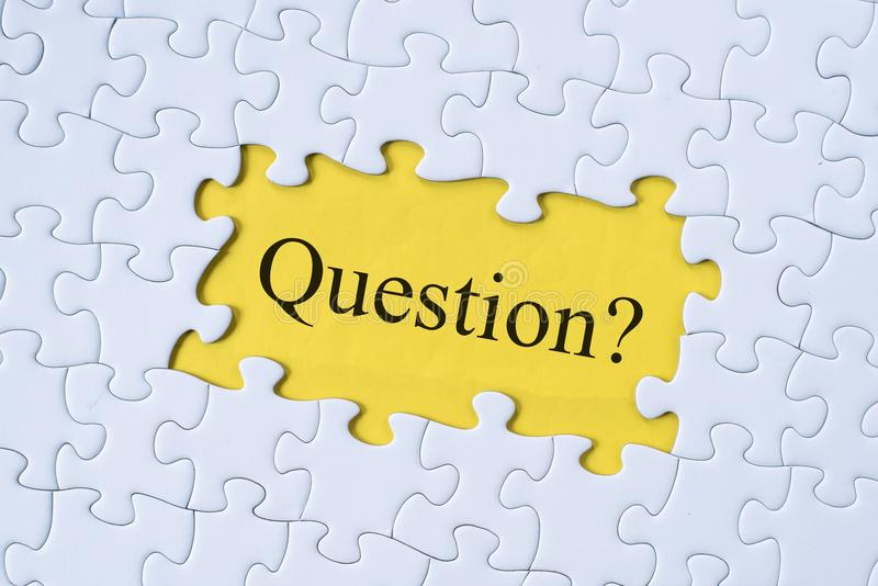 Palabra de la pregunta en rompecabezas con el fondo amarillo imagenes de archivo